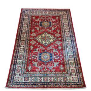 tapis d'orient fond rouge à motif géométrique kazak